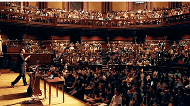 Image of CS50 lecture with david Malan on stage